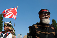 Men in Imperial era military uniforms march with a Japanese battle flag at Yasukuni Shrine. On August 15th every year people gather at Yasukuni Shrine to commemorate the end of the Pacific War. Notionally a call for remembrance and continued peace it is also a Mecca for right wing nationalist including  the paramilitary Uyoku Dantai. Tokyo, Japan, August 15th 2009