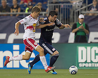 New England Revolution forward Milton Caraglio (9) dribbles down the wing as New York Red Bulls defender Chris Albright (3) pressures. In a Major League Soccer (MLS) match, the New England Revolution tied New York Red Bulls, 2-2, at Gillette Stadium on August 20, 2011.