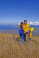 A young newlywed couple on their honeymoon takes a break from their bike ride on Haleakala at a 6,000-ft. elevation. In the background are the West Maui Mountains and the central valley of Maui.