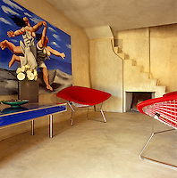 Red Bertoia chairs contrast starkly with the raw plaster walls of this entrance hall in which the painting is inspired by Picasso's 'Deux Femmes Courant sur la Plage'