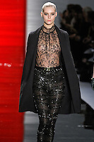 Juju walks runway in a ebony silk crepe duchess coat with embroidered sculpted sleeve over Chantilly lace mock turtleneck blouse and ebony embroidered stretch silk chiffon leggings, from the Reem Acra Fall 2012 Feminine Power collection fashion show, during Mercedes-Benz Fashion Week New York Fall 2012 at Lincoln Center.