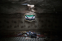 In this Tuesday, Sep. 17, 2013 photo, an opposition fighter rests inside a cave at a rebel camp in the Idlib country side, Syria. (Photo/Narciso Contreras).