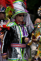 Philadelphia style colorful mummer musician marches and struts at parade.