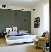 A Serge Mouille wall light dominates the bedroom with a painting by Alberto Cira