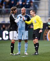 Referee Mark Geiger discusses play with Aurelien Collin (78) of Sporting Kansas City and Jeff Parke (31) of  the Philadelphia Union during the game at PPL Park in Chester, PA.  Kansas City defeated Philadelphia, 3-1.