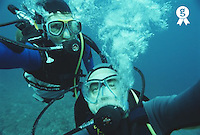 Two scuba divers underwater, close-up, portrait (Licence this image exclusively with Getty: http://www.gettyimages.com/detail/200388001-001 )