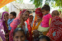 Indian wedding with guests dressed in their finest embellished saris in village of Rohet in Rajasthan, Northern India