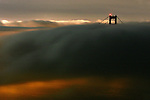 The late summer fog slowly roll in through the Golden Gate during the evening twilight in San Francisco, California.