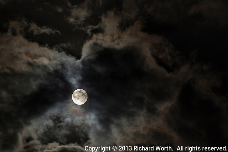 The July full moon, known as the Buck Moon, shines through passing clouds.