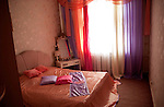 A bedroom in a furnished rental apartment in downtown Minsk is decorated with colored lace curtains, a pink silk bedspread and shiny, pink, flower-stenciled wallpaper on March 13, 2006.