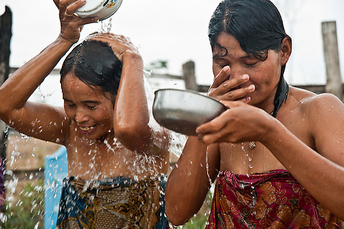 A handpump was provided to a community so far from a source of water that the women could only farm half each day, because they needed to fetch water in the afternoon. In another village at another well, three women bathing are: Chan Sotheat (41) in blue robe; Thuon Sreymom (32) in red robe, and Suy That (39) more heavy set.  The pump serves 100 families, so the ones living close by use it at night so that those living further away can use it during the day.