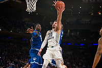 NEW YORK, NY - Thursday March 9, 2017: Andrew Rowsey (#30) of Marquette goes up for a lay-up against Angel Delgado (#31) of Seton Hall as the two schools square off in the Quarterfinals of the Big East Tournament at Madison Square Garden.