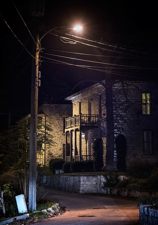 Night scene on street with telegraph pole and wires lit by street light with house and balcony