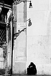 A woman begs for money outside  a church in Venice, Italy.