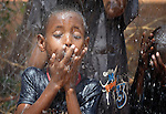 Children play in the spray of an overflowing water tank in the Dadaab refugee camp in northwestern Kenya. Tens of thousands of refugees have fled drought-stricken Somalia in recent weeks, swelling what was already the world's largest refugee settlement.
