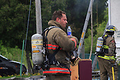 fireman  with bunker and oxygen tank refreshes himself with a drink of bottle water at the scene of a fire