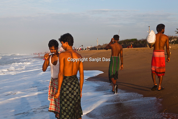 A young man is seen brushing his teeth on Puri Beach along the Bay of Bengal in Puri, Orissa, India. A dip in its salty waters is believed to hold great religious significance, as a result these golden sand beaches sees is a never-ending rush of pilgrims and tourists. Photo: Sanjit Das/Panos