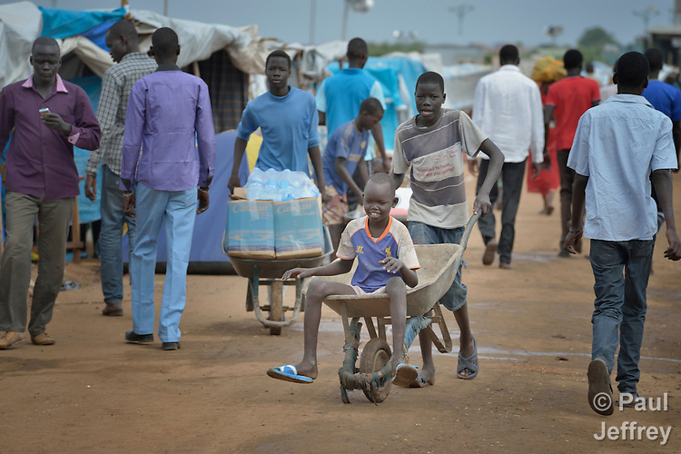 A boy gets a ride in a wheel barrow on a street in a camp for internally displaced families located inside a United Nations base in Juba, South Sudan. The camp holds Nuer families who took refuge there in December 2013 after a political dispute within the country's ruling party quickly fractured the young nation along ethnic and tribal lines. The ACT Alliance is providing a variety of services, including fresh water, sanitation and refuse collection services, to the more than 20,000 people living in the camp.