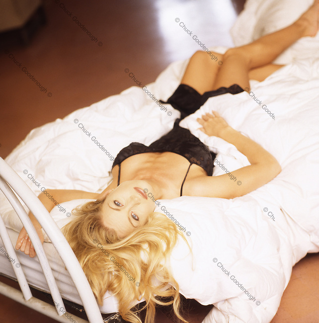 Photo of a blond woman relaxing on a bed in black lingerie looking at the camera.