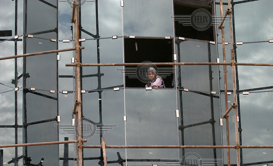 Reconstruction in Kabul. Construction work underway on an office block in the center of town. Worker looking out of window.