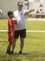 NWA Democrat-Gazette/ANTHONY REYES &bull; @NWATONYR<br /> Juan Barroso, 11, and Garry Jones, with the Springdale police department, discuss strategy Wednesday June 24, 2015 during a soccer game at Jones Elementary School in Springdale. Jones joined other officers for the Sandlot Program where they help mentor the students through play. The officers open up the gymnasium to the children who play and can eat lunch at the school free of charge.