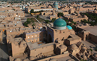 High angle view from the Islam Hodja minaret of the Pahlavan Mahmud Mausoleum, 14th-16th centuries, and in the distance the Matniyaz Divan-begi Madrasah, 1871, and the Kalta Minor, 1855, Khiva, Uzbekistan, pictured on July 4, 2010, at sunrise. The mausoleum centres on the shrine of Pahlavan Mahmud, Khiva's  patron saint , and is also the burial complex of the Qungrat Khans. 19th and 20th century remodeling extended the complex whose blue dome dominates Khiva's skyline rising above its brick building and domes of the adjacent graveyard. Khiva, ancient and remote, is the most intact Silk Road city. Ichan Kala, its old town, was the first site in Uzbekistan to become a World Heritage Site(1991). Picture by Manuel Cohen.