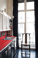 In the kitchen red ceramic tiles on a work surface strike a dramatic note of contrast in an otherwise black and white colour scheme