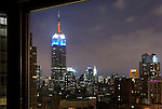 Iconic night view of nearby Empire State Building, lit in red white and blue, and other famous Manhattan buildings, seen through big window in Chelsea neighborhood upper north east corner windows of tall building. NOTE: Faint reflections on windows of brightest lights outside. Very small digital alteration to remove info on signs in distance.