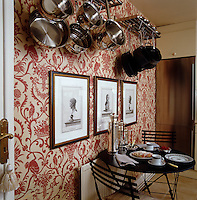 In the small kitchen 19th century neo-classical prints are displayed against Nina Campbell's Tamarin wallpaper