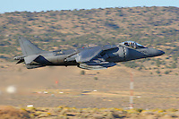 An AV-8B Harrier of the VX-9 Vampires in lowel level flight. Capable of vertical take off's and landings this subsonic fighter is utilized by the Marines as a light ground attack airplane. Powered by a Rolls Royce F402-RR-408 Pegasus vectored thrust turbofan the aircraft has a maximum speed of 629 mph with a range of 685 miles,  Based in China Lake, California, The VX-9 Vampires mission includes operational evaluation of attack, fighter, and electronic warfare aircraft, weapons systems and equipment, and to develop tactical procedures for their employment. Photographed 09/06.