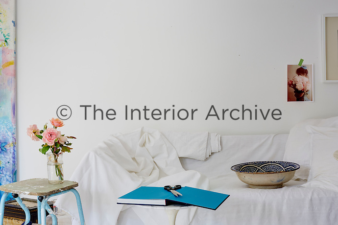 A sofa draped in a white sheet with a paint-spattered step stool as an impromptu side table occupies one wall of the living room