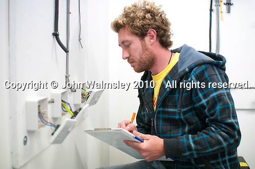 Student electrician making notes on the wiring of three sockets, Able Skills, Dartford, Kent.