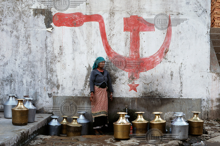A woman collects water from a tap next to a communist symbol painted onto a wall.