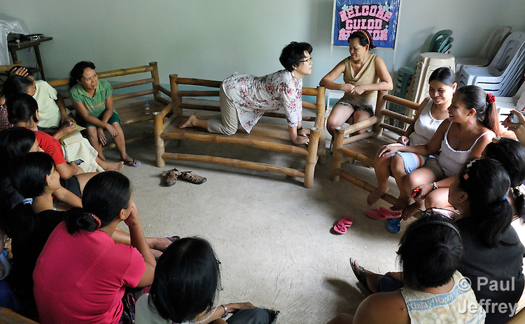 The Rev. Grace Choi is a United Methodist missionary serving in the Philippines, where she is community health worker in the outreach programs of Harris Memorial College. A nurse and a native of Korea, she also teaches piano and voice at the music department of the school. Here she talks about stretching during a discussion of health concerns with a group of women in the Upper Javier neighborhood of the town of Taytay, where Choi carries out health work. .