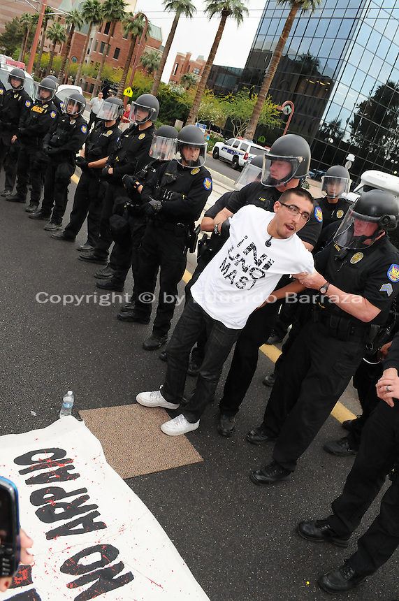 Phoenix, Arizona. April 25, 2012 - Tony Verdugo, one of the six protesters who blocked Central Avenue, was the first to be arrested by Phoenix Police Officers. About 500 people protested the controversial law on the same day U.S. Supreme Court justices heard legal arguments on the Arizona vs. United States case. At the end of the march, six activists blocked Central Avenue by sitting in the middle of the street. They all were arrested by the Phoenix Police Department and taken to the Fourth Avenue County Jail. Photo by Eduardo Barraza © 2012