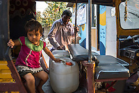 A child plays in her father's rickshaw while waiting for him to buy water at the iJal water station in Gorikathapalli, a remote village in Warangal, Telangana, India, on 22nd March 2015. Safe Water Network works with local communities that live beyond the water pipeline to establish sustainable and reliable water treatment stations within their villages to provide potable and safe water to the communities at a nominal cost. Photo by Suzanne Lee/Panos Pictures for Safe Water Network