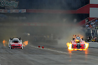 Jun. 19, 2011; Bristol, TN, USA: NHRA funny car driver Cruz Pedregon (right) has a fire alongside Bob Tasca III during eliminations at the Thunder Valley Nationals at Bristol Dragway. Mandatory Credit: Mark J. Rebilas-