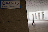 A man with a briefcase walks towards the entrance to the Tokyo Metroplolitan Government building with a sign pointing to the South Obsevatory for tourists. Shinjuku, Tokyo, Japan Wednesday, January 7th 2009