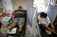 Diabetic patients getting their feet treated at the Nauru Center of Public Health. Feet of Diabetic often gets damaged due to the loss of sensitivity...Nauru has the world's highest level of type 2 diabetes, with more than 40% of the population affected. Life expectancy on Nauru in 2006 was 58 years for males and 65 years for females..Nauru is the world's fattest country, with 94% of its population being overweight. One of the main reason is eating habits of Nauruans. .They rarely cook. Traditional food includes fish and coconut. But these days they especially enjoy Spam and Corned Beef and eat a lot of rice. Nauruans do not grow any vegetables...Nauru, officially the Republic of Nauru is an island nation in Micronesia in the South Pacific.  Nauru was declared independent in 1968 and it is the world's smallest independent republic, covering just 21square kilometers..Nauru is a phosphate rock island and its economy depends almost entirely on the phosphate deposits that originate from the droppings of sea birds. Following its exploitation it briefly boasted the highest per-capita income enjoyed by any sovereign state in the world during the late 1960s and early 1970s..In the 1990s, when the phosphate reserves were partly exhausted the government resorted to unusual measures. Nauru briefly became a tax haven and illegal money laundering centre. From 2001 to 2008, it accepted aid from the Australian government in exchange for housing a Nauru detention centre, with refugees from various countries including Afghanistan and Iraq..Most necessities are imported on the island..Nauru has parliamentary system of government. It had 17 changes of administration between 1989 and 2003. In December 2007, former weight lifting medallist Marcus Stephen became the President.