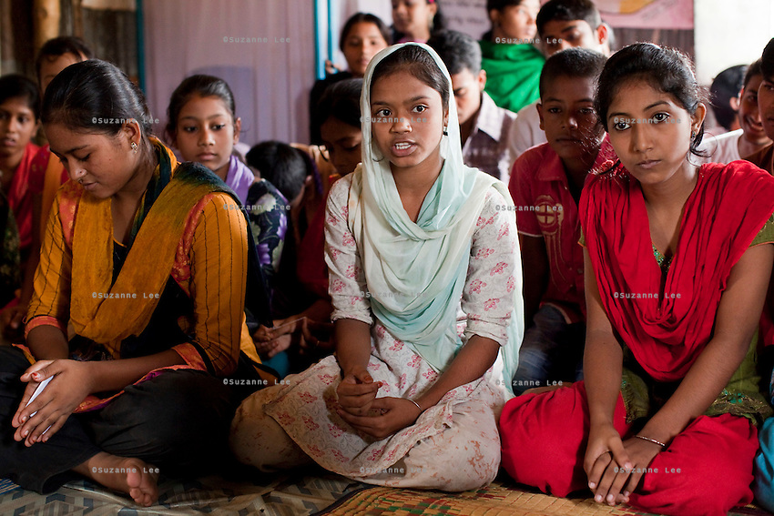 """Rina Akhter Meghla (14, baby blue scarf) speaks of her ordeal during a monthly meeting of a Children's Group in Bhashantek Basti (Slum) in Zon H, Dhaka, Bangladesh on 23rd September 2011. """"I was about to be wed. The groom was already selected. I told my parents that I didn't want to get married now because I just will be a servant to my husband. I wanted to be independent."""" Her parents had said that they wanted to marry her off because she was watching too much television and not doing well in school, after which she promised to stop watching TV and improve her grades. Her ambition is to be a police inspector. The Bhashantek Basti Childrens Group is run by children for children with the facilitation of PLAN Bangladesh and other partner NGOs. Slum children from ages 8 to 17 run the group within their own communities to protect vulnerable children from child related issues such as child marriage. Photo by Suzanne Lee for The Guardian"""