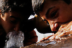 Young Iraqi boys drink water leaking from a water main in the al-Maamil neighborhood, located on the outskirts of Baghdad, Iraq.