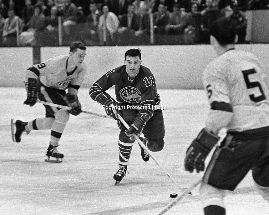 Seals #11 John Brenneman skates against the LA Kings.Kings #9 Real Lemieux, and #5 Dave Amadio. .1968 photo/Ron Riesterer