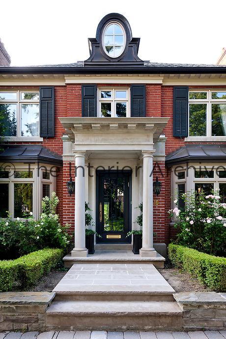 A grand stone portico flanked by a pair of columns heralds the entrance to this red-brick town house