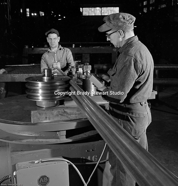 Client: The Pittsburgh Piping Company<br /> Ad Agency:<br /> Product: Fabricated Steel Pipe<br /> Location: On location<br /> <br /> View of operator and helper bending pipe with the new Pedrick Production Bender machine.  The manufacturer is the Pedrick Tool &amp; Machine Company of Philadelphia Pennsylvania.