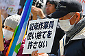 Tokyo, Japan - March 11: A man holds a sign, which says &quot;Don't abandon the nuclear decontamination workers,&quot; at a demonstration against nuclear power plants in front of Tokyo Electric Power Company at Chiyoda, Tokyo, Japan on March 11, 2012. As this day was one year anniversary of Great East Japan Earthquake and Tsunami, there were many demonstrations held in the city. .