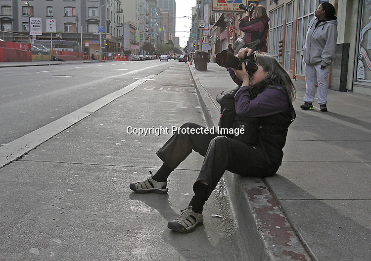 A photographer finds the perfect angle to shoot a photo in the Tenderloin district of San Francisco, CA.