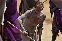 Bugu has a dispute over a woman and challenges his rival to a Donga (stick fight).  When the fighting actually begins there is ritualized posturing that culminates with two men beating the crap out of each other by wailing on their opponents with their long penis shaped sticks. The men brutally battle and sometimes die in the fight.