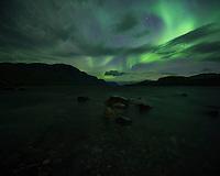 Northern lights shine over lake Langas at STF Saltoluokta Fjällstation, Kungsleden trail, Lapland, Sweden