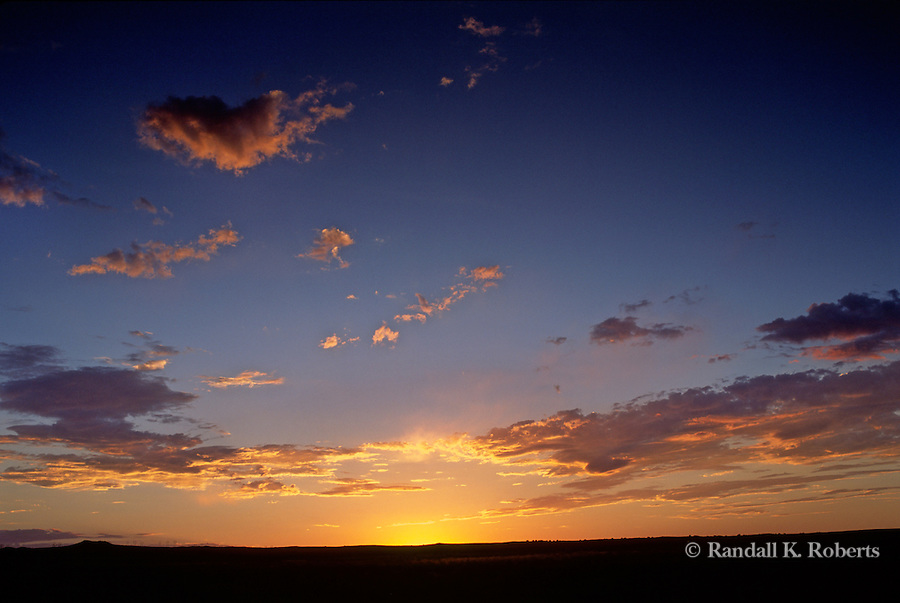 The sunset dips below the western horizon creating a tapestry of gold, orange and blue in the sky west of Albuquerque, New Mexico