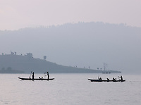 Small local wooden boats travelling across calm waters of Lake Bunyonyi, South Western Uganda